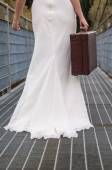 Bride walking on the bridge with her suitcase — Stock Photo
