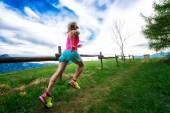 Blonde girl athlete runs a mountain path in the green grass — Foto Stock