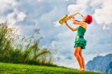 Young saxophonist (woman with the red hair) playing saxophone in
