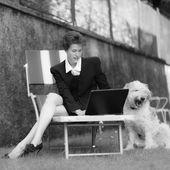 Žena pracuje v počítači v zahradě se psem — Stock fotografie