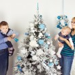 Happy family of four persons decorating christmas tree — Stock Photo #54010061