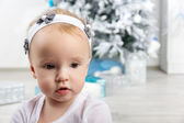 Little girl in front of christmas tree looking sideways — Stock Photo