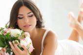 Beautiful bride holding nuptial bouquet — Stock Photo