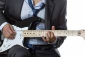 Man in suit playing electric guitar isolated on white — Stock Photo