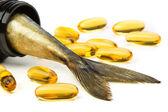 Fish oil capsules and fish tail in brown jar — Stock Photo