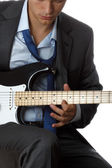 Man in suit and tie playing electric guitar — Stock Photo