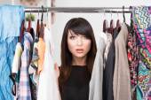 Portrait of young confused woman in front of a wardrobe — Stock Photo