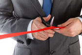 Businessman in suit cutting red ribbon with pair of scissors iso — Stock Photo