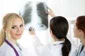 Female medicine doctor with two colleagues looking at x-ray pict — Stock Photo