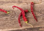 Red hot dry chili peppers on old wooden table — Foto de Stock
