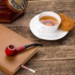 Постер, плакат: Ivory tea cup with sweet cookie tobacco pipe old telephone and