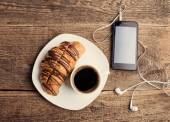Having coffee and croissants with smartphone and headphones — Foto de Stock