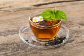 Glass Cup Tea with camomile flower and Mint Leaf, on brown woode — Stock Photo