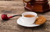 Ivory tea cup with sweet cookie, old telephone and tobacco pipe — Stock Photo
