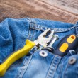 Strong pliers, screw, and screwdrivers in his pocket jeans — Stock Photo #70670521
