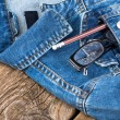 Glasses and pencil in pocket of denim jacket on wooden backgroun — Stok fotoğraf #70671061
