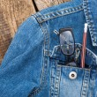Glasses and pencil in pocket of denim jacket on wooden backgroun — Stok fotoğraf #70671089