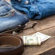 Dirty jeans, money and belt on wooden floor — Stock Photo #70671171