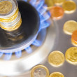 Blue flames of natural gas burning from a gas stove with euro coins — Stock Photo #70674881