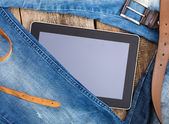 Jeans around mobile tablet pc on old wooben background — Foto Stock