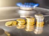 Blue flames of natural gas burning from a gas stove with euro coins — Stock Photo