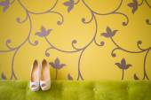 White wedding shoes with a bow and diamonds on a heel on a green — Stock Photo