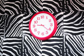 Red clock showing 9:20 on a zebra style wall — Stock Photo