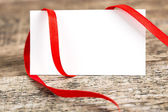 Close up of card note with ribbon on wooden desk — Stock Photo