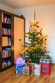 Decorated Christmas tree with gifts in room — Stock Photo