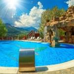 Beautiful swimming pool with beach bar and waterfall — Stock Photo #78438184