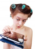 Surprised young woman in a bath towel and hair curlers with tablet computer in her hands. Close-up. — Stockfoto