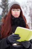 Girl with a book in a snowy park — Stockfoto