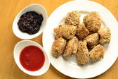 Fried chicken in sesame with tomato sauce and apple chutney — Stock Photo