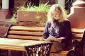 Blonde woman reading a book - yellow retro — Stock fotografie