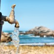 Current water flowing from tap against rocky beach — Stock Photo #70716575