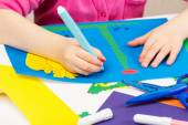 Child makes application of colored paper — Stock Photo