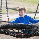 Happy Boy Swinging on a Big Round Swing — Stock Photo