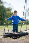 Boy standing on a large swing. — Stock Photo