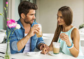Young couple talking and drinking coffee — Stock Photo