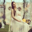 Pregnant woman sitting on swing — Stock Photo #70947397