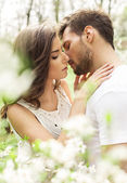 Kissing couple in the blooming garden — Stock Photo