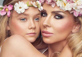 Mother and daughter with flower garland — Stock Photo