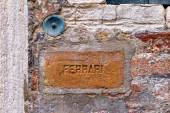 Brass doorbell to enter the house with the label in brick  — Stock Photo