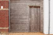 Old wooden wall with a door between the two houses — Stock Photo