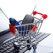 Car and key in shopping trolley — Stock Photo