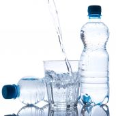 Glass and bottles with fresh water — Stock Photo