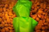 Roasted almonds with green bags — Stock Photo