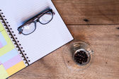 Coffee cup on the table with diary and glasses. — Stock Photo