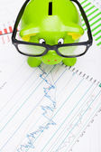 Green piggy bank over stock market chart - view from top — Stock Photo