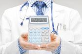 Doctor holdling in his hand calculator - studio shoot — Stock Photo